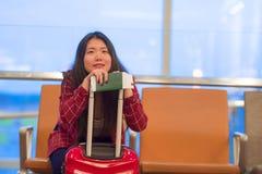 Piękna i szczęśliwa Azjatycka Koreańska turystyczna kobieta czeka lot uśmiecha się ch z podróży walizką w lotniskowym obsiadaniu  obraz stock