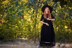 Piękna imbirowa czarownicy kobieta w kapeluszu na lasowym tle Halloweenowy kostiumu pojęcie kosmos kopii fotografia royalty free