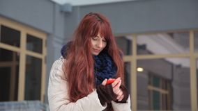 Piękna imbirowa czerwona z włosami kobieta używa mądrze telefon technologię app przy miasto ulicami żyje miastowego szczęśliwego  zdjęcie wideo