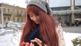 Piękna imbirowa czerwona z włosami kobieta używa mądrze telefon technologię app przy miasto ulicami żyje miastowego szczęśliwego  zbiory
