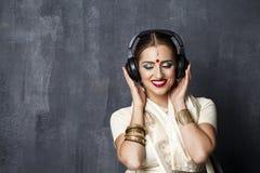 Piękna Indiańska kobieta słucha muzyka na hełmofonach Obrazy Royalty Free