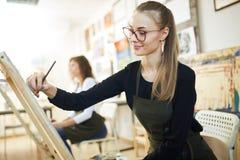 Piękna jasnogłowa dziewczyna w szkłach ubierających w czarnej bluzce i fartuchu siedzi przy sztalugą i maluje obrazek w fotografia stock