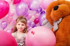 Piękna kędzierzawa dziewczyna pozuje wśród różowych balonów Fotografia Royalty Free