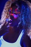 Piękna kędzierzawa dziewczyna pozuje w pozafioletowym świetle Obraz Royalty Free