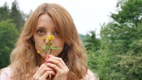 Piękna kędzierzawa miedzianowłosa kobieta trzyma żółtego dzikiego kwiatu Portret przeciw górom i lasowi Lato zdjęcie wideo