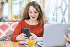 Piękna kędzierzawa rudzielec dziewczyna z piegami z zdziwionym szczęśliwym wyrażeniowym mieniem z oba rękami mądrze telefon zdjęcia stock