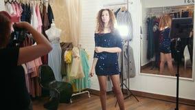 Piękna kędzierzawa z włosami kobieta w wieczór sukni pozuje dla fotografa w sklepu odzieżowego butiku zdjęcie wideo