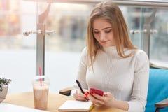 Piękna Kaukaska blondynki dziewczyna siedzi przy stołem, robi niektóre notatkom w bufecie, prepasres dla egzaminu Powabny uczeń w zdjęcie stock