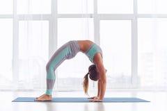 Piękna kobieta ćwiczy backbend joga asana Urdhva Dhanurasana - Oddolna obszycie łęku poza przy joga studiiem obrazy stock
