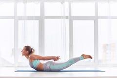 Piękna kobieta ćwiczy joga asana Salabhasana - szarańczy poza przy joga studiiem zdjęcie stock