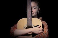 Piękna kobieta ściska jej gitarę Zdjęcia Stock