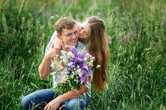 Piękna kobieta ściska mężczyzna obsiadanie na trawie w łące z bukietem dzicy kwiaty Zdjęcia Stock