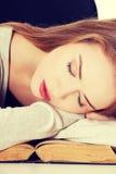 Piękna kobieta śpi na książce fotografia royalty free