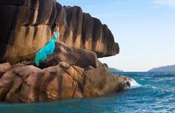 Piękna kobieta, błękit długa suknia, skały i morze Seychelles, Obraz Stock