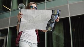 Piękna kobieta bada miasto mapę z powiększać z oznakującymi przypadkowymi ubraniami i szkłami - szkło zbiory wideo
