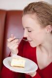 Piękna kobieta cieszy się cheesecake fotografia stock