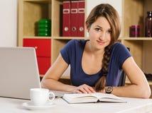 Piękna kobieta czyta laptop i używa zdjęcie stock