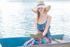 Piękna kobieta czyta z rzędu łódź na jeziorze zdjęcie royalty free