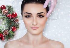 Piękna kobieta dostaje twarzowego masaż w zdroju salonie Zbliżenie kobiety twarz i nowego roku wianek obrazy royalty free