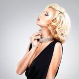 Piękna kobieta dotyka szyję z kędzierzawą fryzurą Zdjęcia Royalty Free