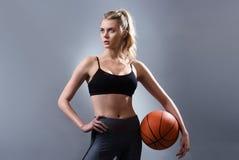 Piękna kobieta gracza koszykówki pozycja i mienie koszykówki piłka Fotografia Stock