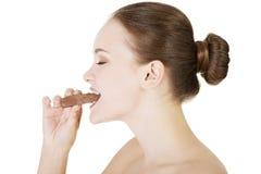 Piękna kobieta gryźć czekoladowego baru Zdjęcia Stock