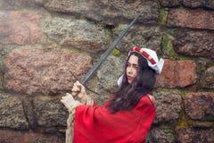 Piękna kobieta huśtał się kordzika blisko kamiennej ściany obrazy stock