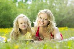 Piękna kobieta i dziewczyna bawić się na pastylce w naturze, kłama na koc w trawie obrazy royalty free