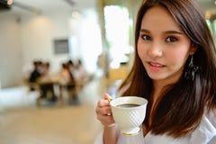 Piękna kobieta i trzymać filiżankę kawy w jej ręce w plamy tła sklep z kawą Obrazy Royalty Free