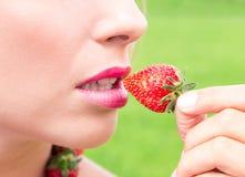 Piękna kobieta je świeże truskawki w ogródzie Fotografia Stock