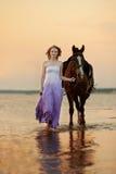 Piękna kobieta jedzie konia przy zmierzchem na plaży Młody gira zdjęcia stock