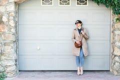 Piękna kobieta jest ubranym cajgi i okop stoi przeciw ścianie na miasto ulicie, Przypadkowa moda, elegancki codzienny spojrzenie obrazy stock