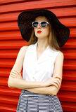 Piękna kobieta jest ubranym czarnego słomianego kapelusz, okulary przeciwsłonecznych i paskującą spódnicę nad czerwienią, Zdjęcie Stock