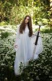 Piękna kobieta jest ubranym długą biel suknię trzyma kordzika Zdjęcia Royalty Free