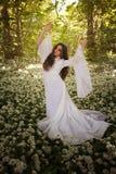 Piękna kobieta jest ubranym długiego biel sukni tana w lesie Obraz Stock