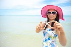 Piękna kobieta jest ubranym i trzyma rozgwiazdy kapeluszy okulary przeciwsłonecznych i plażę Obraz Stock