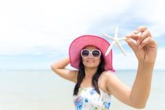 Piękna kobieta jest ubranym i trzyma rozgwiazdy kapeluszy okulary przeciwsłonecznych i plażę Obrazy Royalty Free