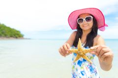 Piękna kobieta jest ubranym i trzyma rozgwiazdy kapeluszy okulary przeciwsłonecznych i plażę Zdjęcie Stock