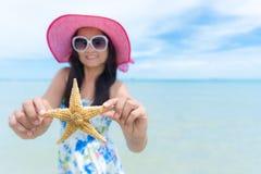 Piękna kobieta jest ubranym i trzyma staBeautiful kobiety kapeluszy okulary przeciwsłonecznych i plażę jest ubranym i trzyma star Obrazy Royalty Free