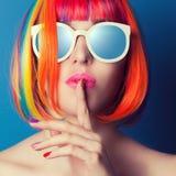 Piękna kobieta jest ubranym kolorową perukę i białych okularów przeciwsłonecznych agains Zdjęcie Stock