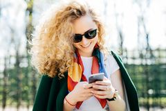 Piękna kobieta jest ubranym okulary przeciwsłonecznych i zieloną kurtkę trzyma mądrze telefon w ona wyszukuje internet cieszy się fotografia royalty free