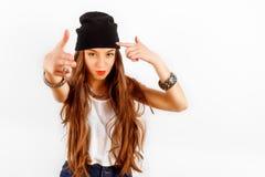 Piękna kobieta jest ubranym w czarnym kapeluszu i białej koszulce stoi blisko biel ściany, przedstawienia armatni palce ręki Zdjęcie Stock