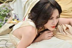 Piękna kobieta kłama puszek z kwiatami plenerowymi Zdjęcie Royalty Free