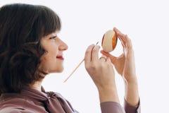 Piękna kobieta maluje Easter jajko w świetle, odosobnionym z spac Zdjęcie Stock