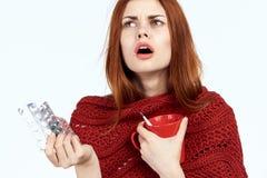 Piękna kobieta na białym odosobnionym tle trzyma kubek i pigułki, choroba, choroba, grypa, portret, emocje zdjęcie stock