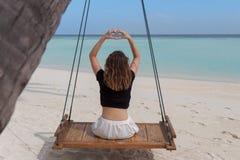 Piękna kobieta na huśtawce dołączającej palma obramia rękę w kierowego kształt, palcowa serce rama Kryształ - jasna woda Maldives obrazy royalty free