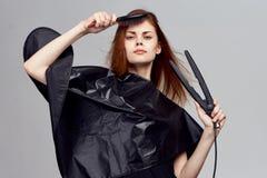 Piękna kobieta na szarym tle trzyma gręplę, fryzowania żelazo, styl, fryzura Zdjęcia Royalty Free