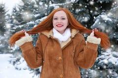 Piękna kobieta na zimie plenerowej, śnieżni jedlinowi drzewa w lesie, długi czerwony włosy, jest ubranym barankowego żakiet Zdjęcia Stock
