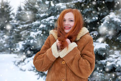 Piękna kobieta na zimie plenerowej, śnieżni jedlinowi drzewa w lesie, długi czerwony włosy, jest ubranym barankowego żakiet Zdjęcie Stock