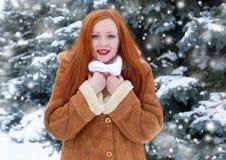Piękna kobieta na zimie plenerowej, śnieżni jedlinowi drzewa w lesie, długi czerwony włosy, jest ubranym barankowego żakiet Obrazy Royalty Free